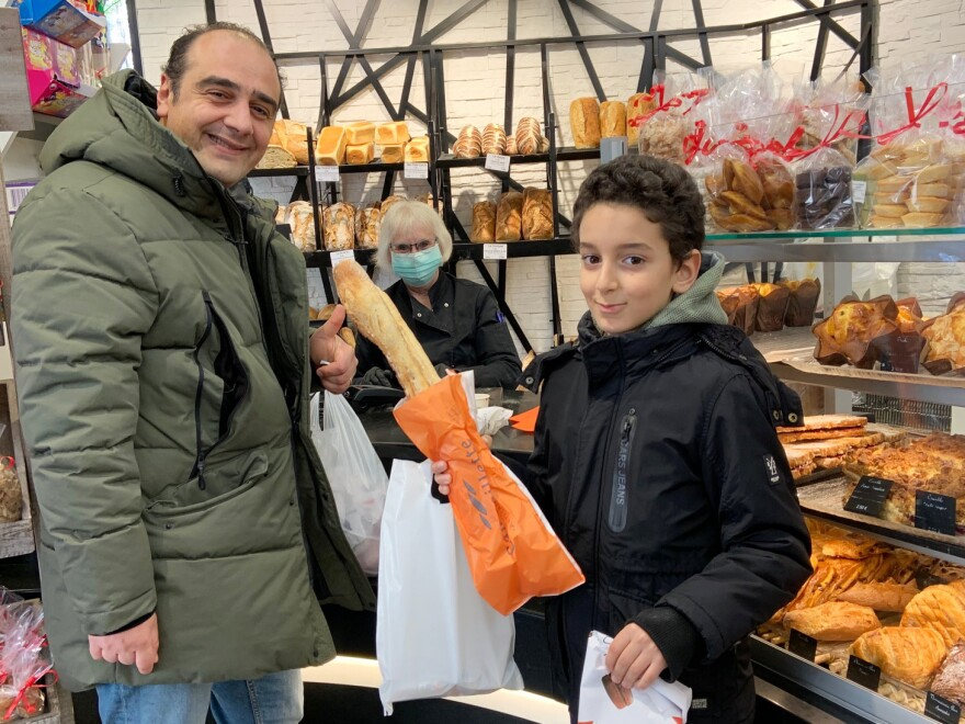 Veterinarian Nour Ahmed Mirali and his 9-year-old son Marwan pick up a baguette and a cake.