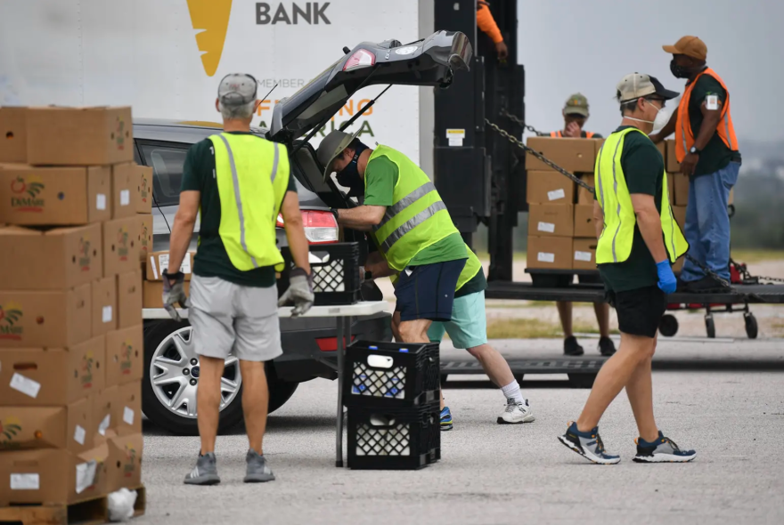 Volunteers load boxes of food into the drunk of a car.