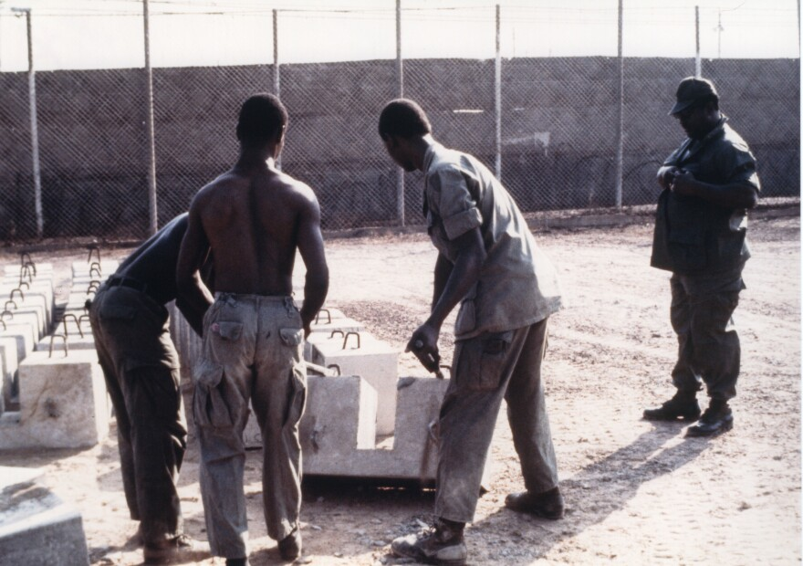 Prisoners on work duty, making aircraft security blocks.