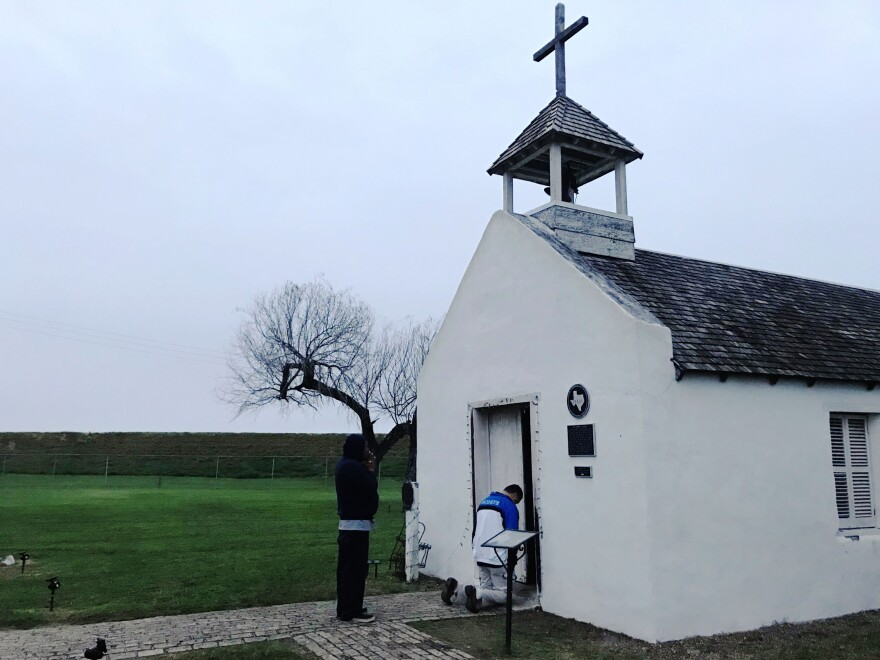 Two men pray at an early morning service at La Lomita chapel, a historical landmark in Mission, Texas.