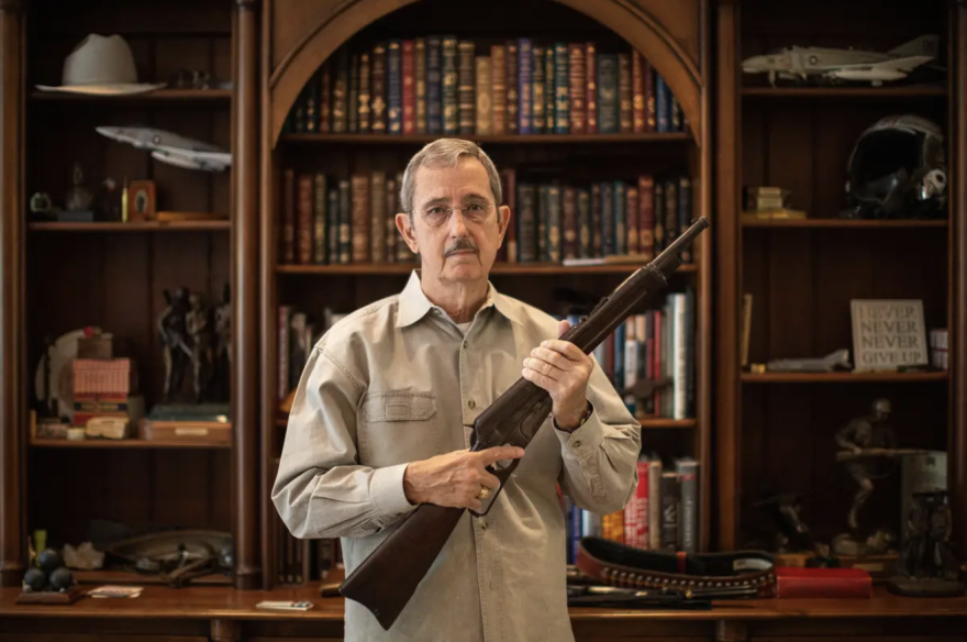 Former Land Commissioner Jerry Patterson holds up a Winchester Model 1895 carbine, a model favored by the Texas Rangers.