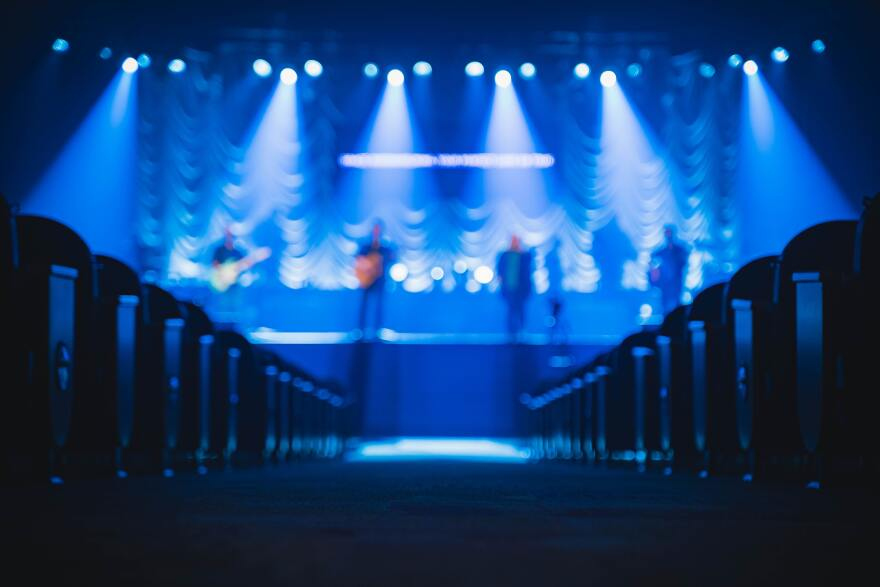 People standing on stage with blue lights at an empty venue.