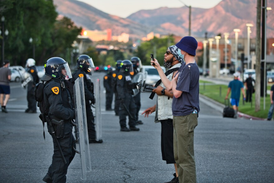 A photo of protests talking to two officers.