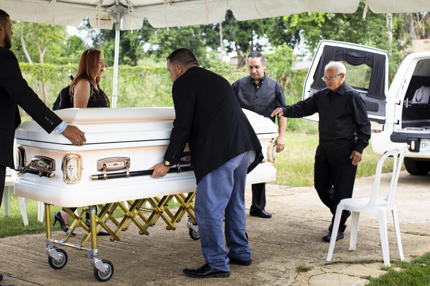 Armando Colón (second from right) helps lift his mother's casket out of the hearse at a cemetery 40 minutes away from Lares.