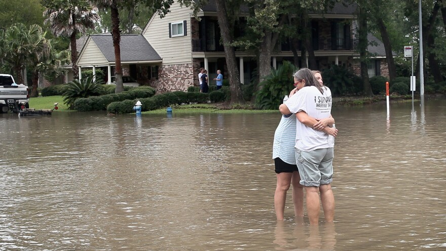 HOUSTON, TX - AUGUST 30: Friends reunite in the middle of a flooded intersection as water continues to rise in their neighborhood following Hurricane Harvey on August 30, 2017 in Houston, Texas. Harvey, which made landfall north of Corpus Christi August 25, has dumped nearly 50 inches of rain in and around Houston. (Photo by Scott Olson/Getty Images)