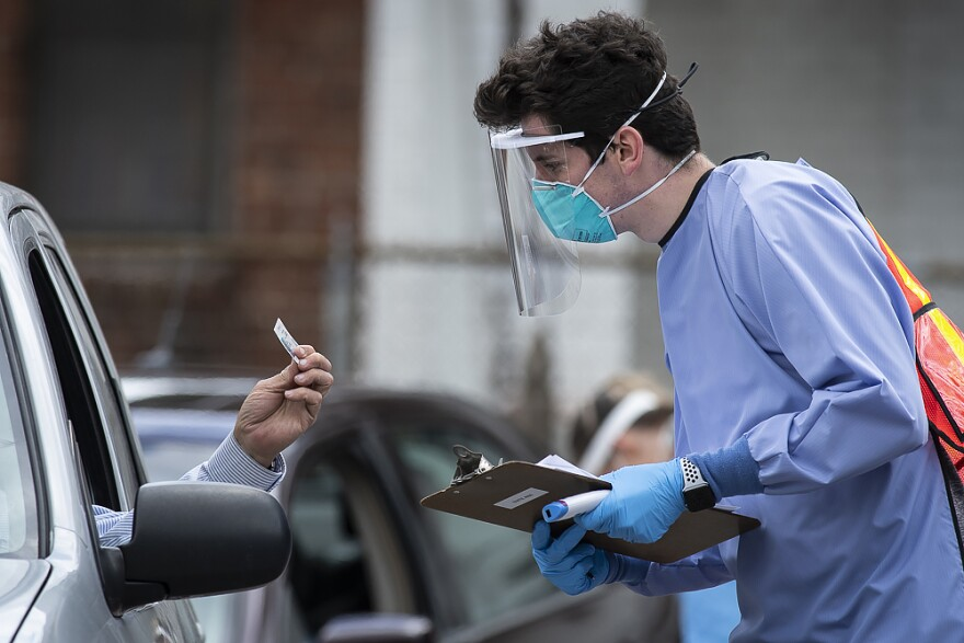 A man dressed in complete personal protection equipment working at a drive-thru COVID -19 testing site.