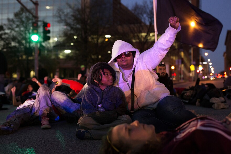 Brandi Johnson and 8-year-old Michael Conner observe a four- and-half-minutes of silence in honor of Michael Brown during an anti-Trump protest in downtown St. Louis in November 2016.