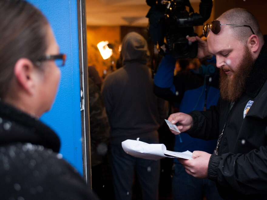 Kurt Britz checks a driver's license at the 3-D Denver Discrete Dispensary on Jan. 1, 2014, the first day recreational marijuana sales were legal in Colorado. Possession remains illegal for those under 21 years old, and statistics show a widening racial gap in arrests for those offenses.
