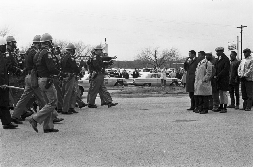 Spider Martin's most well-known photograph, <em>Two Minute Warning,</em> shows marchers facing a line of state troopers in Selma moments before police beat the protestors on March 7, 1965. The day became known as Bloody Sunday.