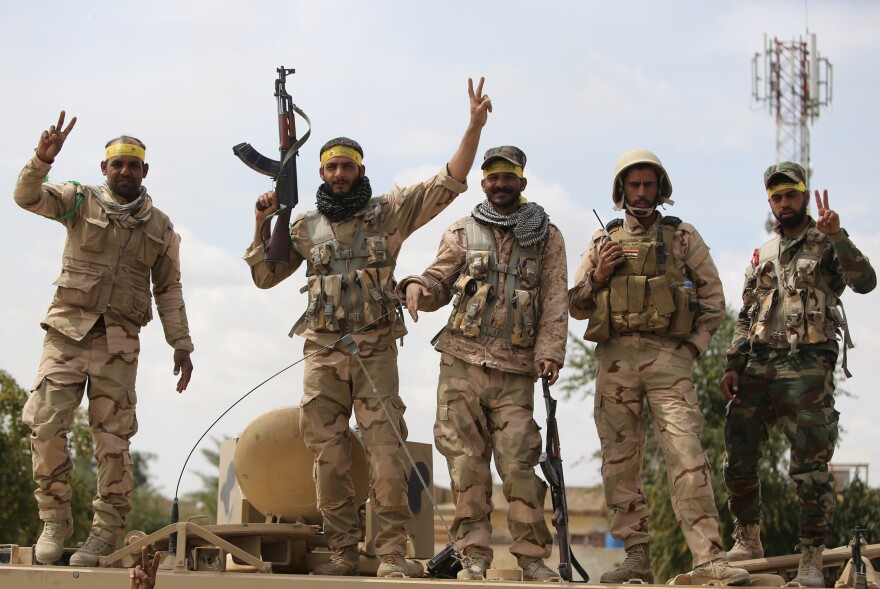 Iraqi Shiite fighters flash the victory sign in Tikrit on Wednesday.