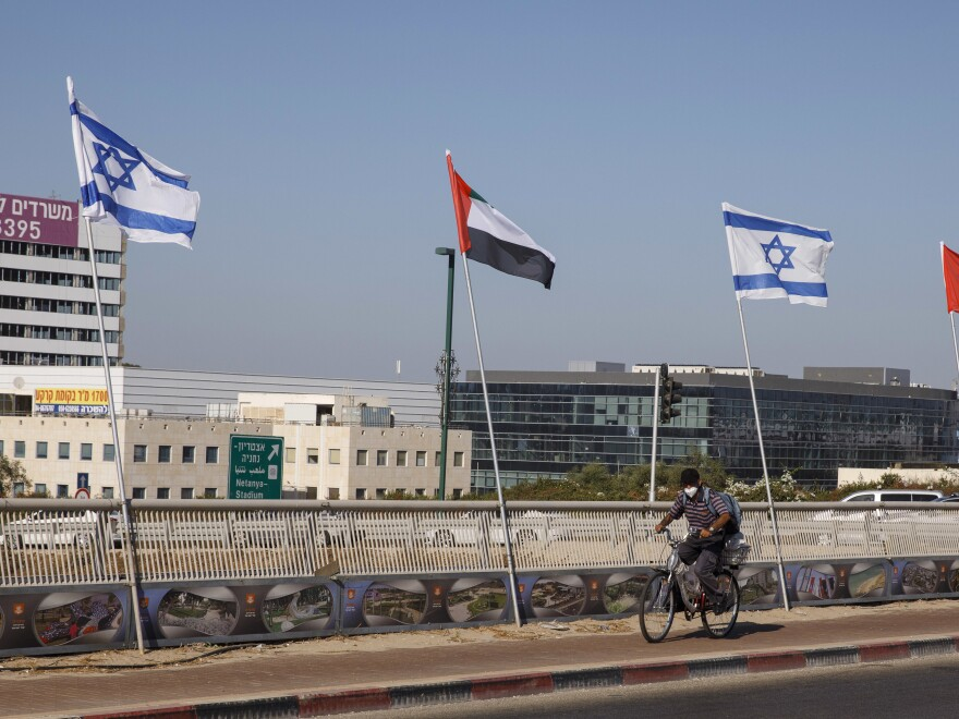 A cyclist rides by Israeli and United Arab Emirates national flags in Netanya, Israel, on Aug. 17.