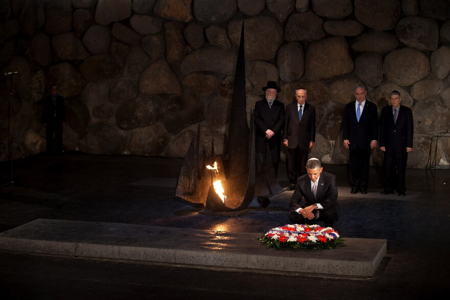 President Barack Obama pays his respects in the Hall of Remembrance in front of Israel's President Shimon Peres, Israel's Prime Minster Benjamin Netanyahu, Chairman of the Yad Vashem Directorate Avner Shalev and Rabbi Yisrael Meir Lau after marines layed a wreath on his behalf during his visit to the memorial on Friday.