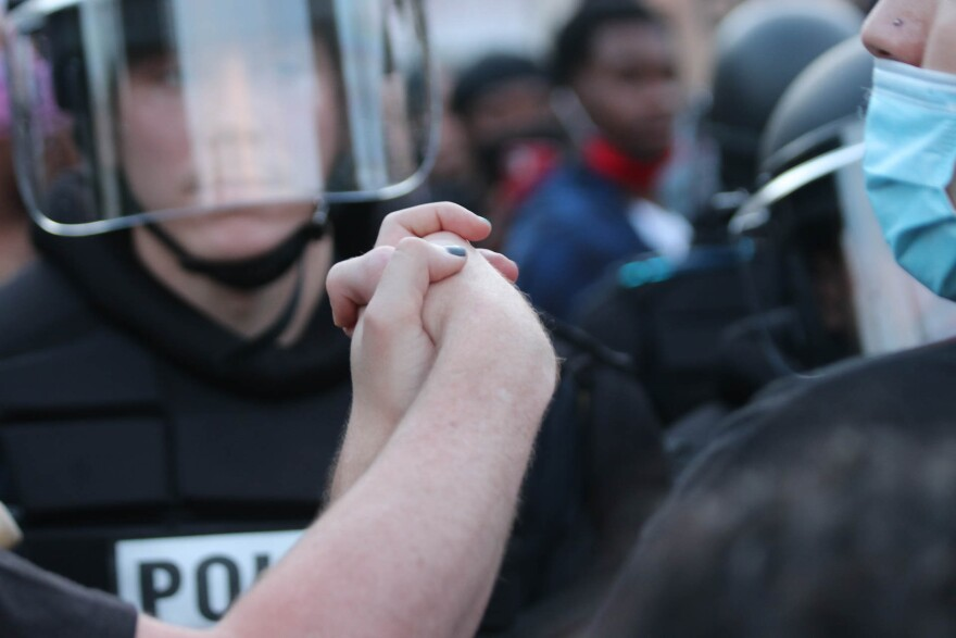 Protesters join hands as they face police officers in San Antonio on May 30, 2020.