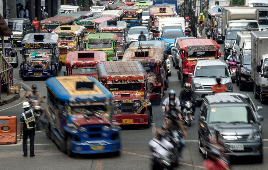 "Jeepneys, often known in the Philippines as ""King of the Road,"" join traffic on a busy street in Manila last May. Authorities are moving to phase them out, citing pollution and safety concerns."