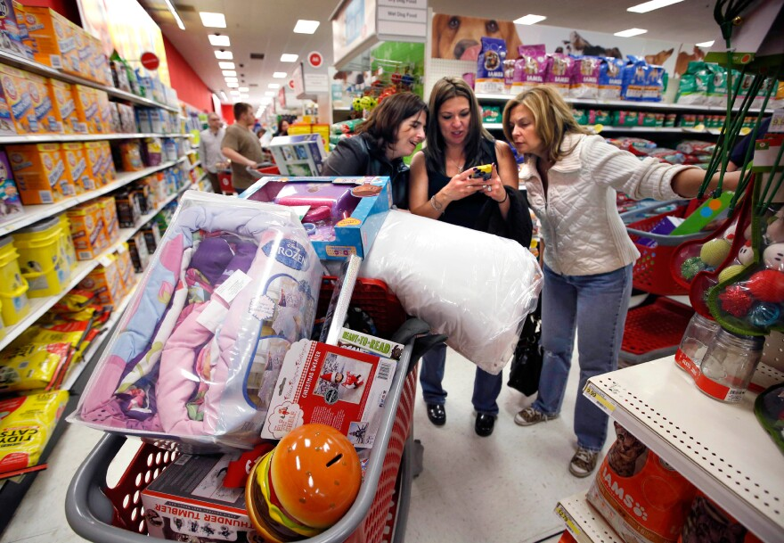 Target shoppers Kelly Foley (from left), Debbie Winslow and Ann Rich use a smartphone to look at a competitor's prices while shopping shortly after midnight on Black Friday, in South Portland, Maine.