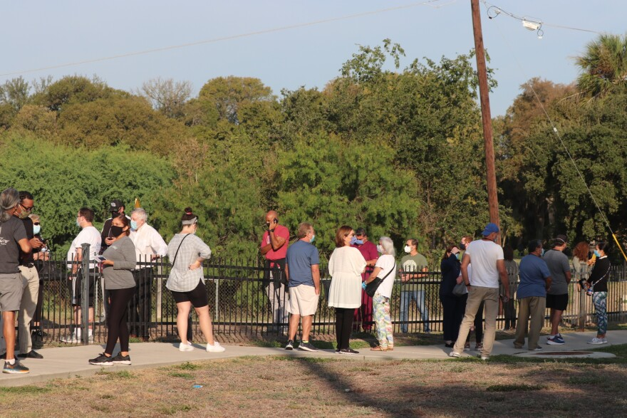 Several voters wait in line at the Lions Field Park polling location of Broadway. The line had several hundred people in it an hour after polls opened on the first day of early voting, Oct. 13, 2020.