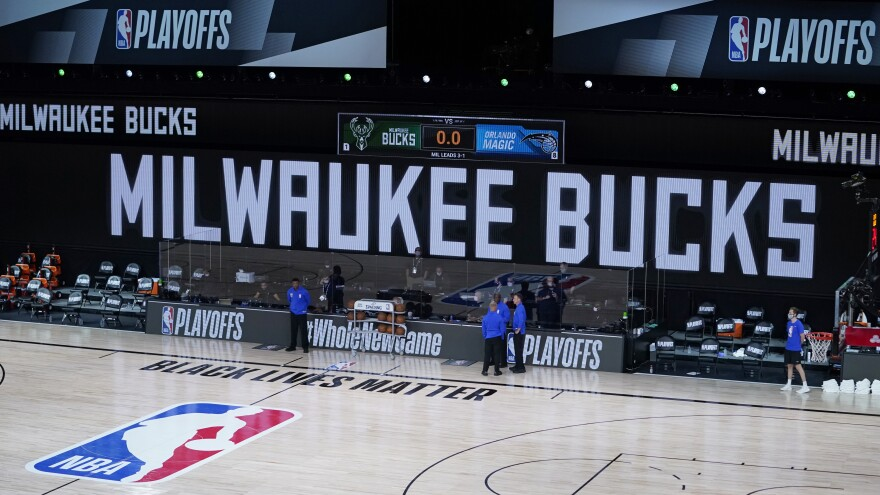 Officials stand beside an empty court at the scheduled start of an NBA playoff game on Wednesday. The Milwaukee Bucks didn't take the floor in protest against racial injustice and the shooting of Jacob Blake.