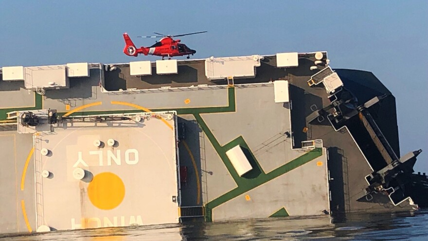 In this image released by the U.S. Coast Guard, a helicopter hovers over the overturned Golden Ray cargo vessel in St. Simons Sound, Ga., on Monday. Twenty of the 24 people on board had been rescued as of Sunday afternoon, when crews were forced to suspend the search because of safety concerns related to a fire on the ship.