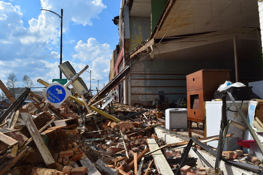 The front of a building is torn off. A hurricane Evacuation Route signs sits on top of the rubble.