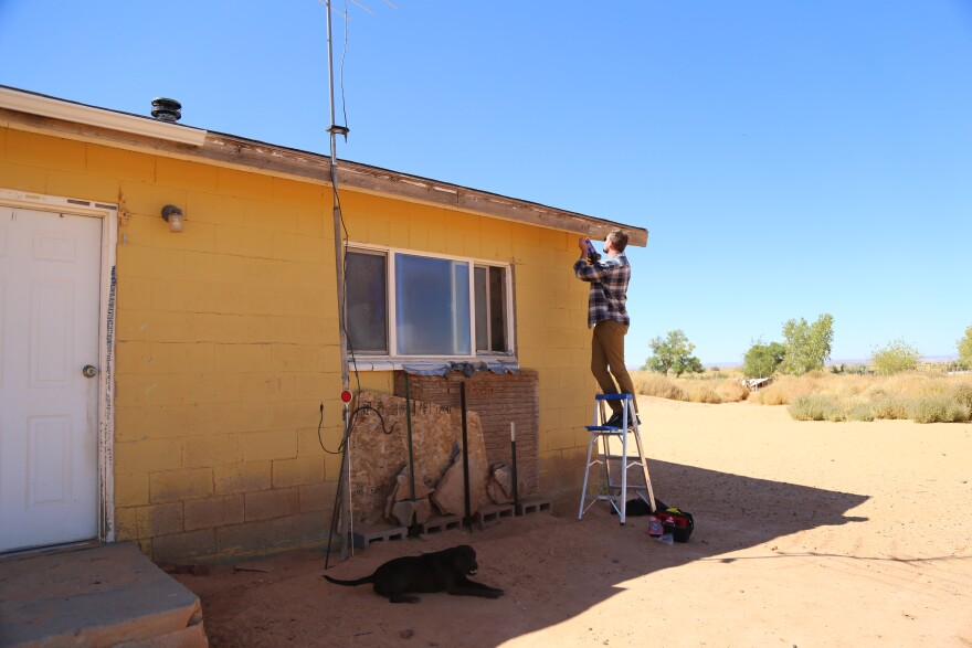 A photo of a man nailing something to a house.