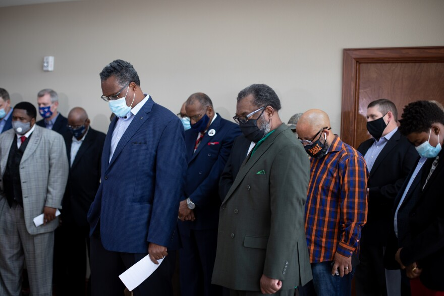 Community faith leaders bow their head in prayer at the start of Wednesday's press conference at the Dallas West Church of Christ, before advocating for the name change of Lamar St. in memory of Botham Jean.