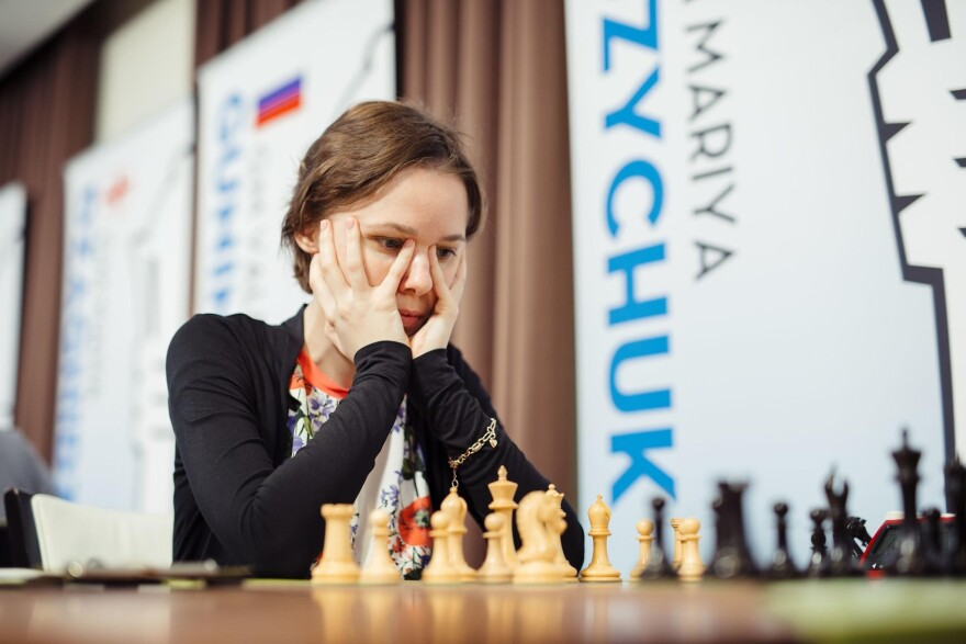Woman focusing on a chess game.