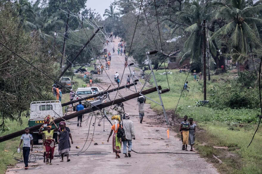 People walk along a main road in Macomia past power lines downed by Cyclone Kenneth. Vehicles could just about get through by driving on the side of the road.