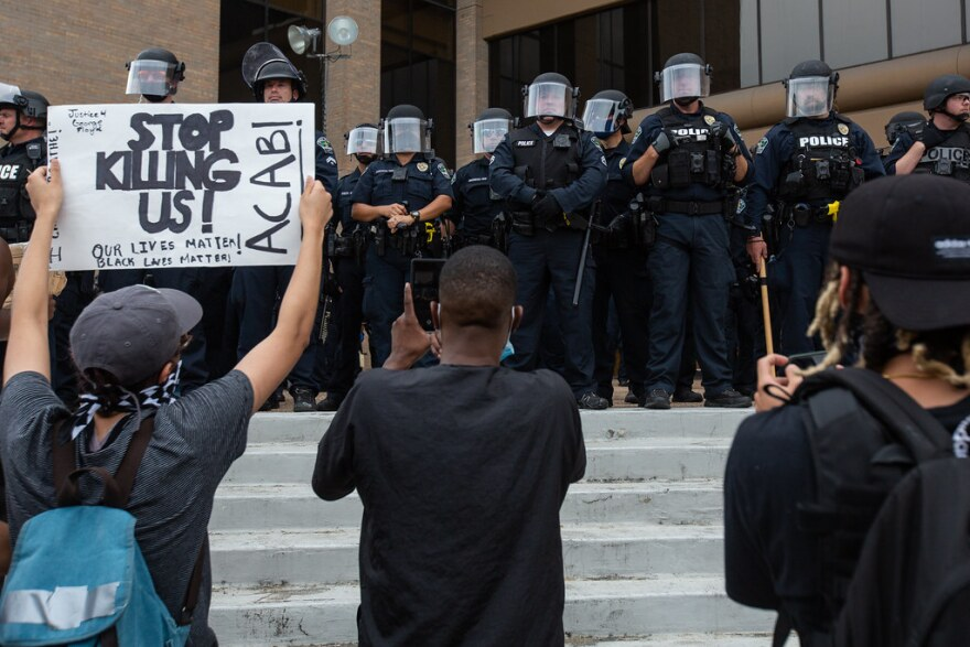 """A protester holds a sign that says """"Stop killing us"""" outside Austin police headquarters."""