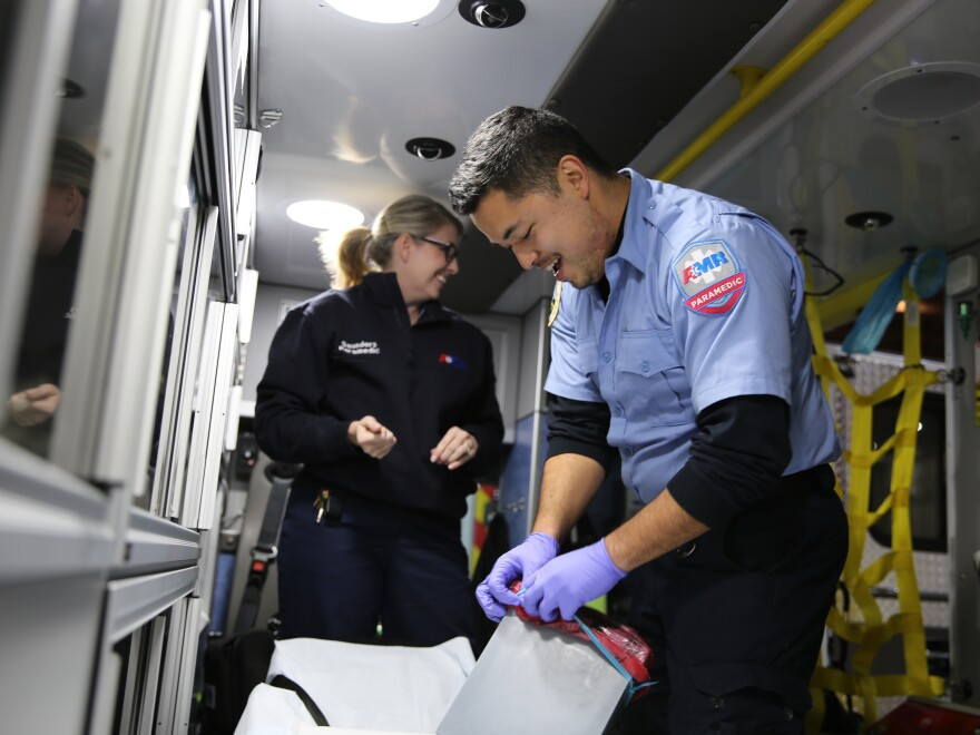 Talitha Saunders and AJ Ikamoto tidy their ambulance at the end of a recent shift. The two work as emergency medical responders in Oregon with American Medical Response in Portland. Leaders there are working to prevent any race-based disparities in treatment.