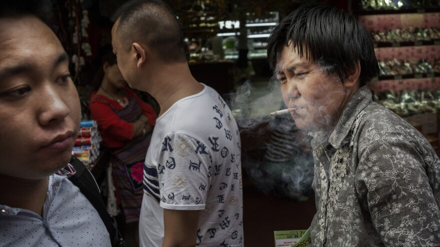 A woman smokes a cigarette in a Beijing shopping market, even though the practice is now banned inside public spaces.