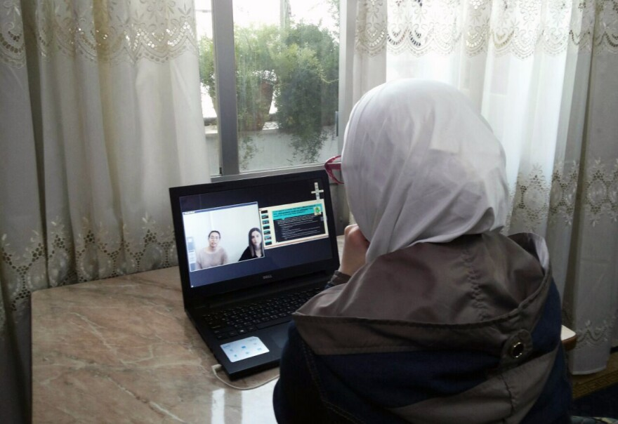 A student in Syria participates in an online English language class. She's one of the few students with a laptop; others use their mobile phone.