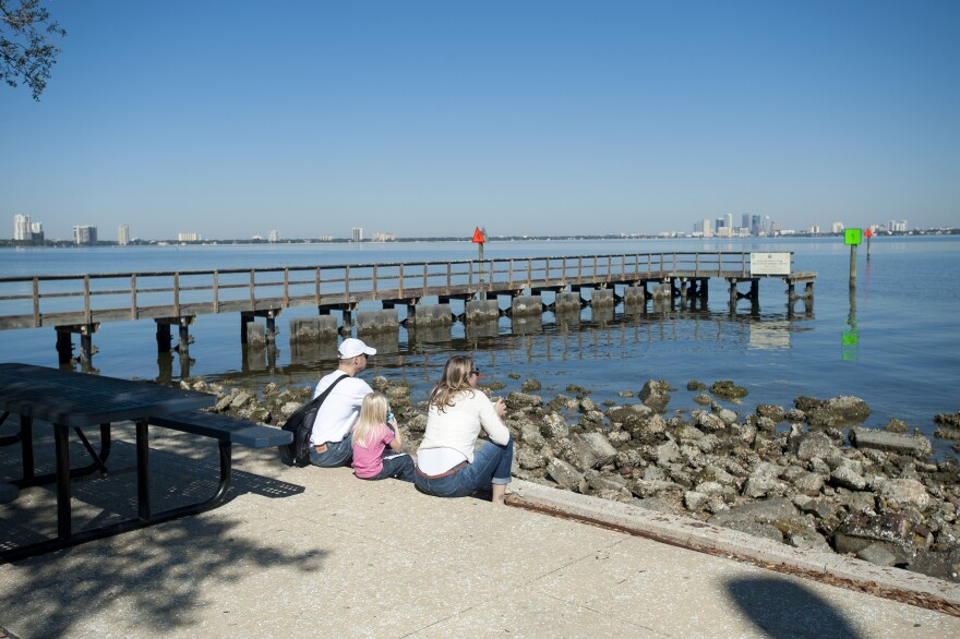people sitting by rocks and water with pier