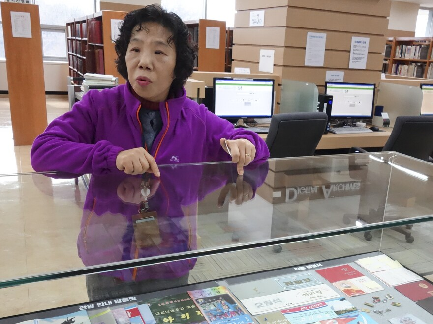 North Korea Information Center librarian Jeong Hui-suk stands over a display of ticket stubs from North Korean theater programs and flights.