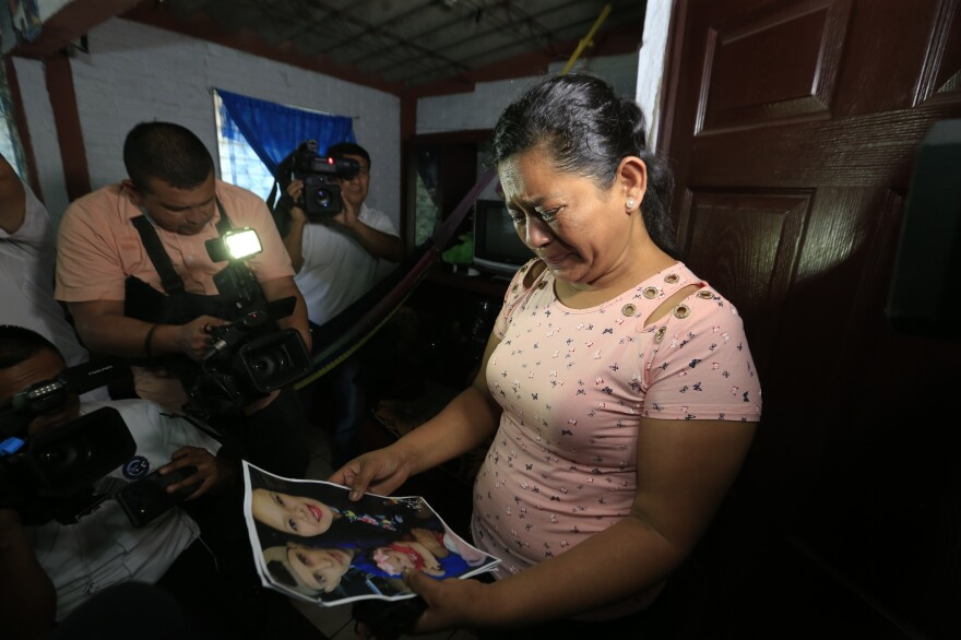 Rosa Ramírez cries as she looks at photos of her son Óscar Alberto Martínez Ramírez, 25, and granddaughter Valeria, nearly 2, while speaking to journalists at her home in San Martín, El Salvador, on Tuesday. The drowned bodies of her son and granddaughter were found Monday morning on the banks of the Rio Grande.