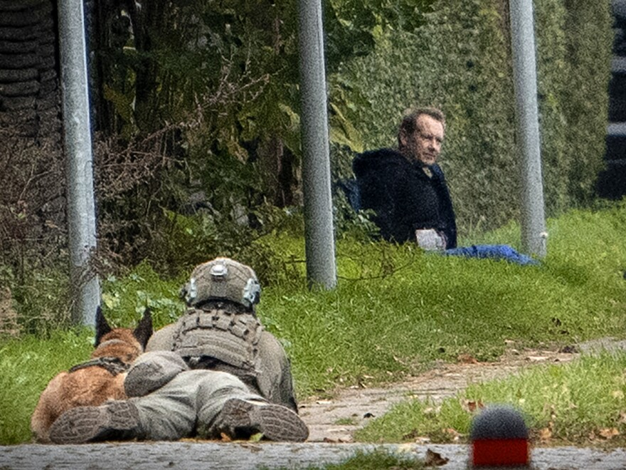 A police marksman and his dog observes convicted killer Peter Madsen threatening police with detonating a bomb while attempting to break out of jail in Albertslund, Denmark on Tuesday.