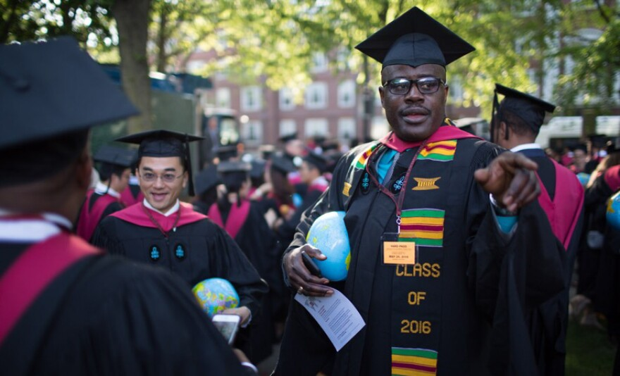 """Gregory """"Buster"""" Coleman in his cap and gown. Each graduate of the Kennedy School of Government carried an inflatable globe."""