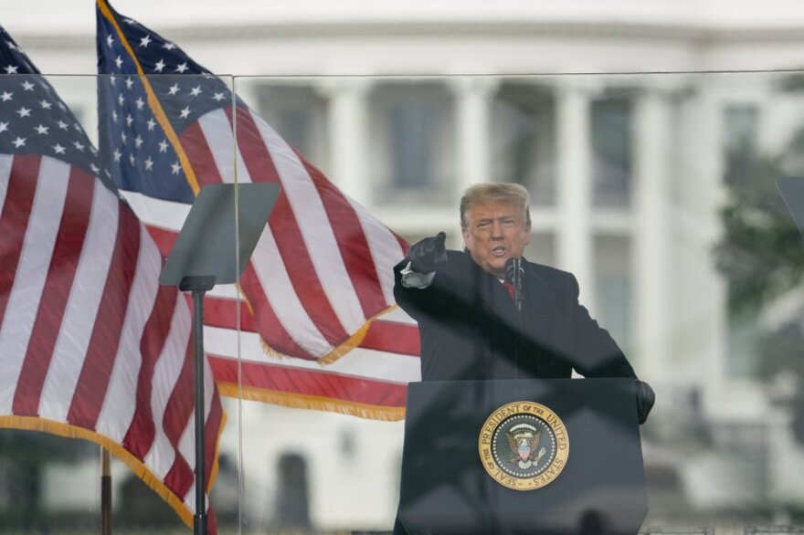 President Trump points to a crowd while standing behind a wall of Plexiglass with American flags flapping behind him.