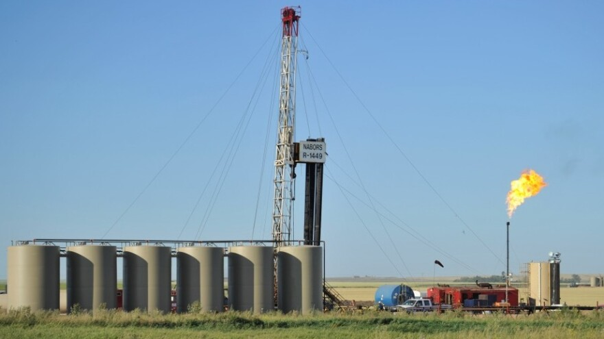 Natural gas is burned off next to an oil well being drilled at a site  near Tioga, N.D., in August. U.S. oil production started increasing a few years ago and is predicted to continue to rise, reducing the country's dependence on oil imports.