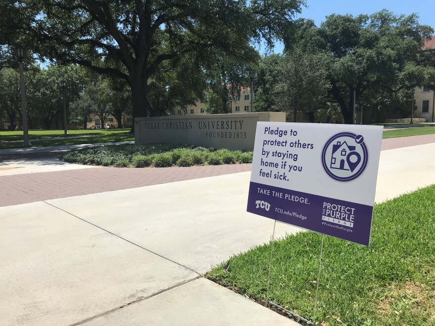 In this photo, a sign on TCU's campus urges people to stay home if they feel sick. It stands on a grassy lawn with a big stone Texas Christian University sign nearby.