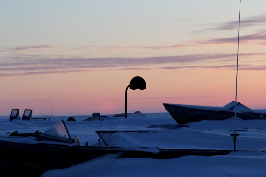 A basketball hoop stands near boats buried in the winter snow. Shishmaref, Alaska, is just a few dozen miles below the Arctic Circle, and in the depths of winter the sun rises close to noon.
