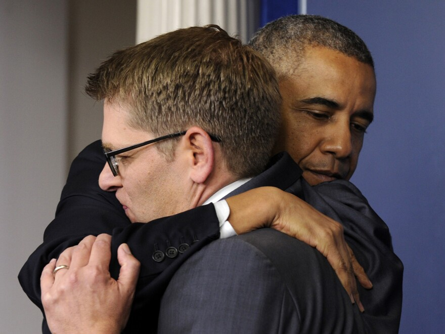 President Obama gives White House press secretary Jay Carney a hug after announcing that Carney will step down next month.