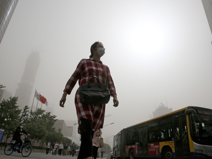 A woman wearing a face mask walks on a street as Beijing is hit by polluted air and sandstorms on May 4.