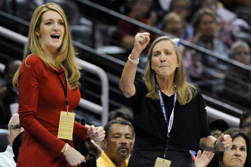 Kelly Loeffler (left), with Mary Brock, cheers the Atlanta Dream on courtside during a 2011 game. Now a senator, Loeffler faces a political challenge over her stake in the WNBA franchise in a tough election race.