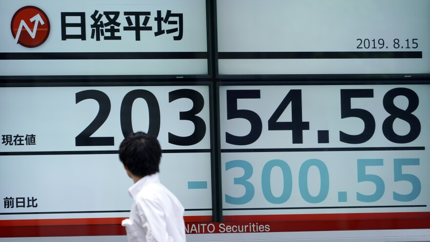 A man looks at an electronic stock board showing Japan's Nikkei 225 index at a securities firm in Tokyo on Thursday.