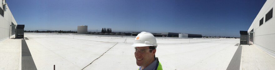 """Paul Hopkins of DuPont Fabros stands on the roof of company's newest Silicon Valley data center. """"It's about the same size and length as a Nimitz aircraft carrier,"""" he says."""