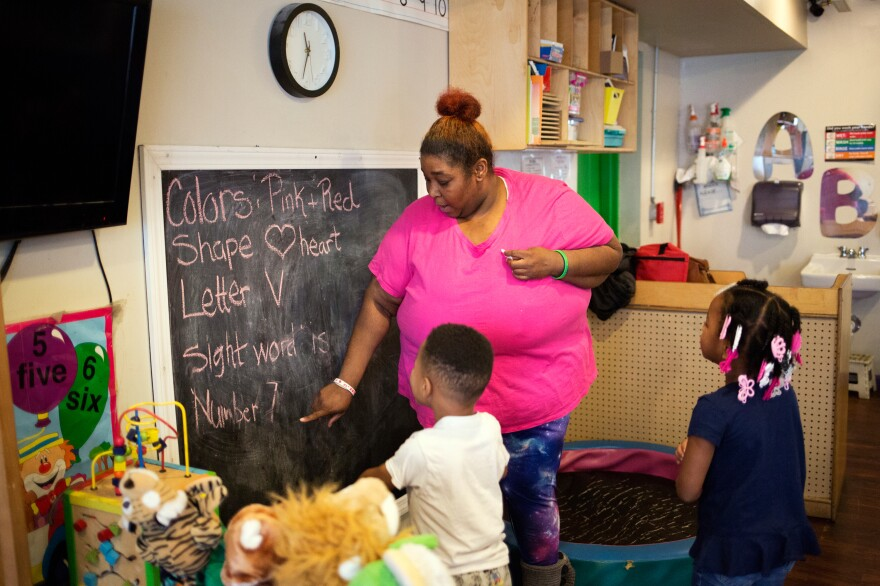 The program's assistant director, Tawanda Brand, works with students at the Little Explorers Learning Center in St. Louis on Jan. 29. After closing temporarily because of the coronavirus, the center re-opened in May for the children of essential workers. All staff members now wear masks.