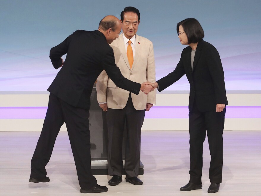 Taiwan's 2020 presidential candidates (from right), President Tsai Ing-wen of the Democratic Progressive Party, the People First Party's James Soong and the Nationalist Party's Han Kuo-yu, greet one another at the start of their televised debate in Taipei on Dec. 29. Taiwan will hold its general elections on Saturday.