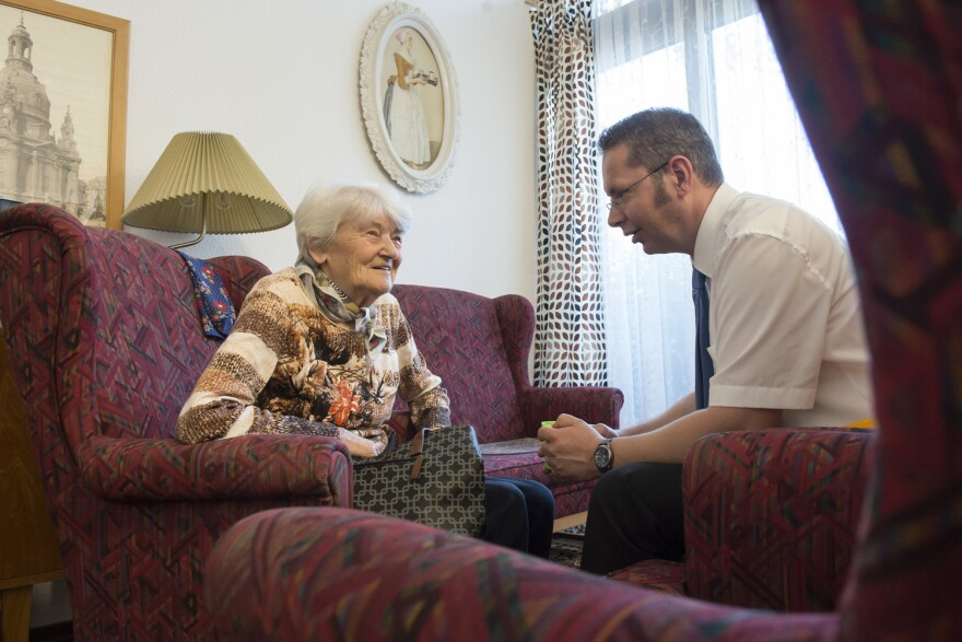 In this May 17, 2017 photo resident Gerda Noack talks with residence director Gunter Wolfram in the Alexa Seniors' Residence in Dresden, eastern Germany. The retirement home has recreated the communist era of the former GDR in two living-rooms to help residents with Alzheimer's and dementia. (AP Photo/Jens Meyer)