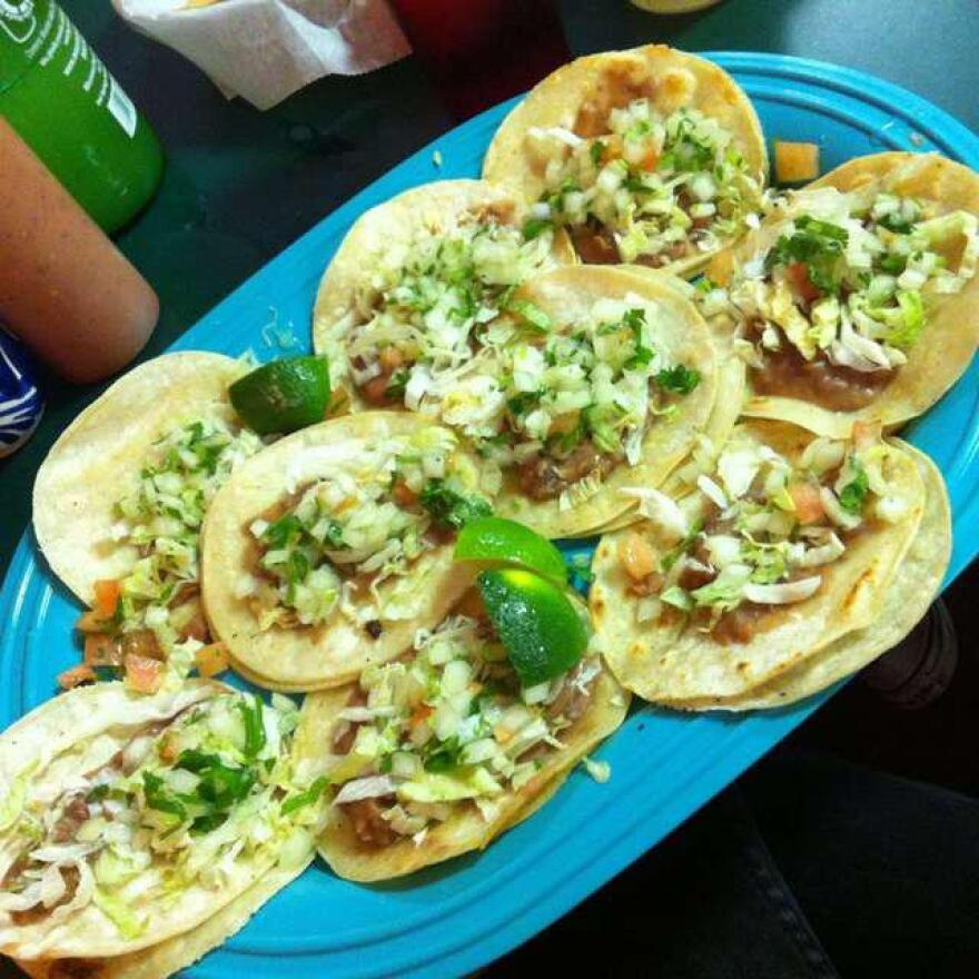 A pile of soft corn tortilla tacos on a bright blue plate.