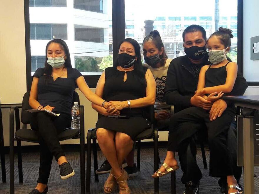 Photo of five people dressed in black sitting and wearing masks